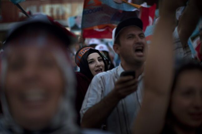 Supporters of Prime Minister Recep Tayyip Erdogan, who is the front-runner in Turkey's presidential election, react as they celebrate the first results in downtown Istanbul, Turkey, Sunday, Aug. 10, 2014. Turks were voting in their first direct presidential election Sunday _ a watershed event in Turkey's 91-year history, where the president was previously elected by Parliament. Prime Minister RecepTayyip Erdogan, who has dominated the country's politics for the past decade, is the strong front-runner to replace the incumbent, Abdullah Gul, for a five-year term. (AP Photo/Emilio Morenatti)