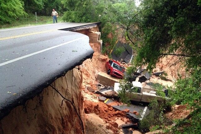 AP10thingsToSee - Vehicles lie at the bottom of a ravine after the Scenic Highway collapsed near Pensacola, Fla., Wednesday April 30, 2014. Nearly 2 feet of rain drenched Escambia and Santa Rosa counties in the span of about 24 hours. (AP Photo/Pensacola News Journal, Katie E. King)