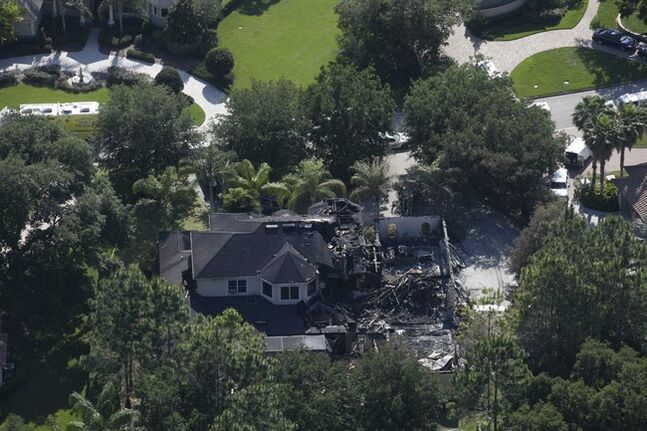 This aerial photo shows the burned out home on Thursday, May 8, 2014 in Tampa, Fla. Authorities have said they think the fire at the five-bedroom home was intentionally set and that they found fireworks inside the home. Police have not said how the blaze started or who might be responsible. The home, which is owned by former tennis star James Blake, was engulfed in flames when firefighters responded Wednesday morning. Neighbors told police they heard explosions coming from it. Blake was renting the house to the a family and was not there at the time. (AP Photo/The Tampa Bay Times, Eve Edelheit) TAMPA OUT; CITRUS COUNTY OUT; PORT CHARLOTTE OUT; BROOKSVILLE HERNANDO TODAY OUT