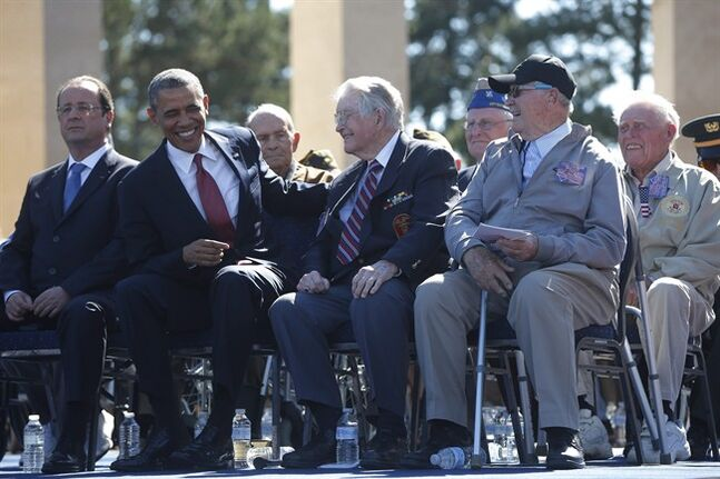 U.S. President Barack Obama, second left, and French President Francois Hollande sit on stage with veterans, at Normandy American Cemetery at Omaha Beach as he participates in the 70th anniversary of D-Day in Colleville sur Mer, in Normandy, France, Friday, June 6, 2014. (AP Photo/Charles Dharapak)