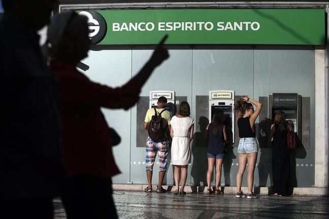 In this July 28, 2014 photo, people use ATMs at a branch of Portuguese bank Banco Espirito Santo in Lisbon. The Espirito Santo family business survived wars, dictatorship, revolution and family feuds for almost 150 years. Now, one of Europe's last banking dynasties is being stripped of its wealth and influence amid accounting irregularities, huge unreported debts, and a police investigation. (AP Photo/Francisco Seco)