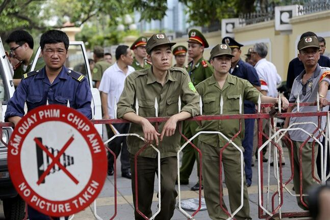 Vietnamese security officers set up a fence outside an area of the Chinese Embassy in Hanoi, Vietnam on Sunday, May 18, 2014. Vietnamese authorities forcibly broke up small protests against China in two cities on Sunday, after deadly anti-China rampages over a simmering territorial dispute risked damaging the economy and spooked a state used to keeping a tight grip on its people. In southern Ho Chi Minh City, police dragged away several demonstrators from a park in the city center. In Hanoi, authorities closed off streets and a park close to the Chinese Embassy and pushed journalists and protesters away. (AP Photo/Na Son Nguyen)