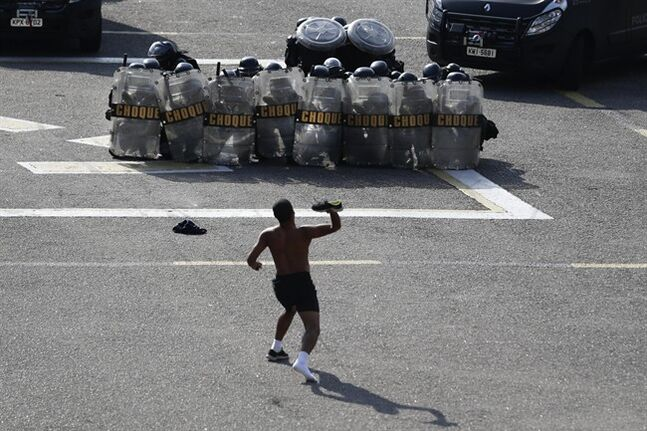 A person posing as a protester throws his shoe at police during a drill to prepare security forces for demonstrations during the upcoming World Cup in Rio de Janeiro, Brazil, Thursday, May 15, 2014. The FBI is helping to train Brazil's civilian police, military officers, municipal guards and firefighters on how to manage demonstrations ahead of the international soccer tournament that starts in June. (AP Photo/Hassan Ammar)
