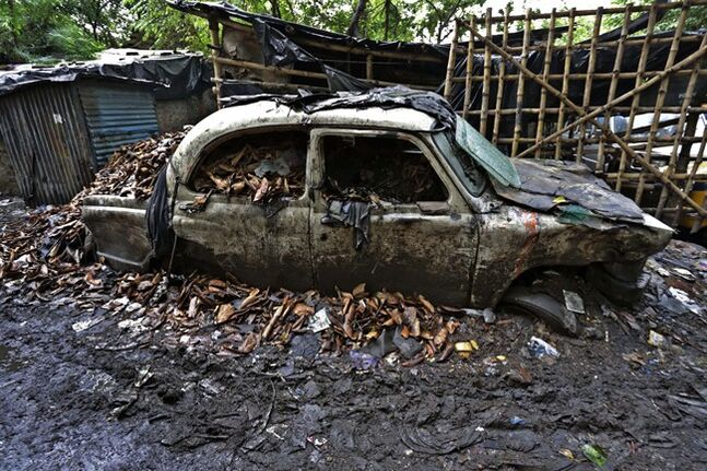 An abandoned Ambassador car lies in mud at a workshop in Kolkata, india, Monday, May 26, 2014. India's oldest car factory has abruptly suspended production of the hulking Ambassador sedan that has a nearly seven-decade history as the car of the Indian elite. (AP Photo/ Bikas Das)