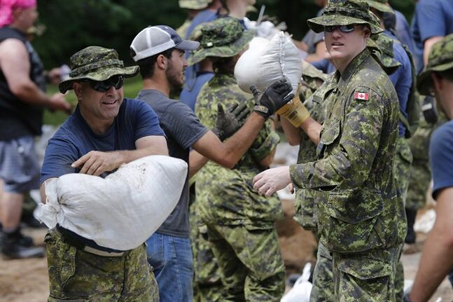 Soldiers from 17 Wing in Winnipeg sandbag in St. Francois Xavier, Man., Tuesday, July 8, 2014. Several days of frantic sandbagging is paying off in southern Manitoba as a crest of flood water is expected to pour through the region. THE CANADIAN PRESS/John Woods