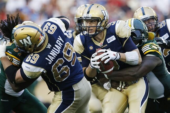Winnipeg Blue Bombers' quarterback Drew Willy (5) gets hauled down by Edmonton Eskimos' Almondo Sewell (90) during the first half of CFL action in Winnipeg Thursday, July 17, 2014. THE CANADIAN PRESS/John Woods