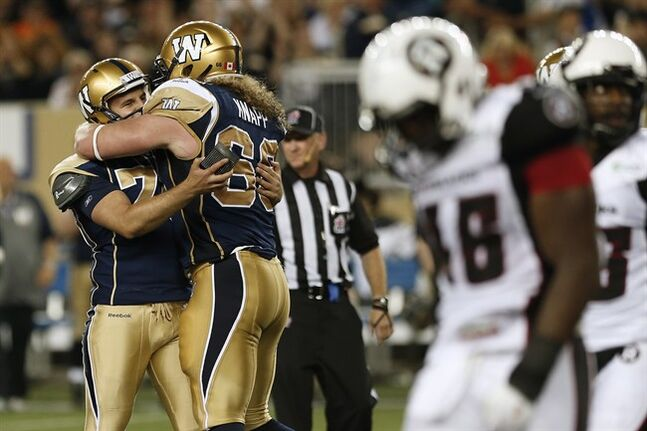 Winnipeg Blue Bombers' Lirim Hajrullahu (70) and Dan Knapp (66) celebrate his field goal against the Ottawa Redblacks during the second half of CFL action in Winnipeg Thursday, July 3, 2014. THE CANADIAN PRESS/John Woods
