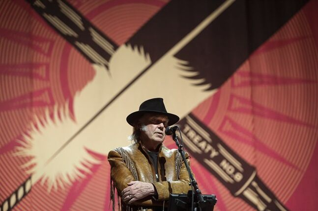 Singer Neil Young speaks during a news conference before the last concert in his