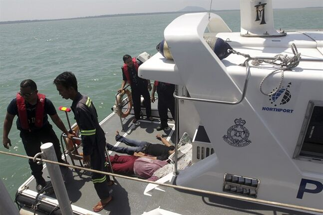 EDS NOTE: GRAPHIC CONTENT - In this photo released by Malaysian Maritime Enforcement Agency, Malaysian marine police officers stand on the deck of a boat after they retrieved bodies of a capsized boat off Sungai Air Hitam in Banting, outside Kuala Lumpur, Malaysia, Wednesday, June 18, 2014. At least 60 people survived when a wooden boat carrying 97 Indonesians capsized and sank early Wednesday after leaving Malaysia's west coast, but 32 others are still missing and five bodies have been recovered, Malaysia's maritime agency said. (AP Photo/Malaysian Maritime Enforcement Agency) EDITORIAL USE ONLY