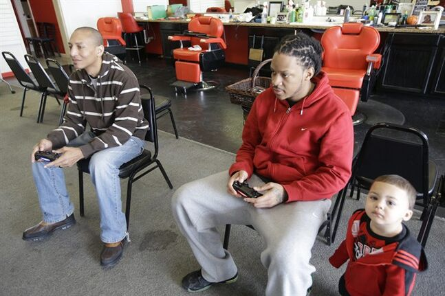 In this Tuesday, Jan. 28, 2014 photo, barbers Tarris Horton, left, and England Wesley play a video game while they wait for customers at Hair on the Floor Barbershop in Covington, Ky. Wesley says business at the barbershop, which depends heavily on walk-in clientele, has been down about 90 percent in the past several weeks. One-year-old Kannon Wesley watches at right. (AP Photo)
