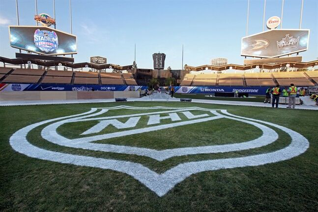 A large NHL logo adorns center field at Dodger Stadium as preparations continue for the upcoming 2014 NHL Stadium Series hockey game at Dodger Stadium in Los Angeles Wednesday, Jan. 22, 2014. The Los Angeles Kings and Anaheim Ducks will play outdoors at Dodger Stadium next Saturday, Jan. 25th. (AP Photo/Nick Ut)