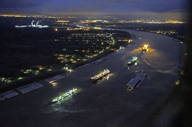 In this aerial photo, river traffic is halted along the Mississippi River between New Orleans and Vacherie, La., due to a barge leaking oil in St. James Parish, La., Sunday, Feb. 23, 2014. The collision happened Saturday afternoon near Vacherie, 47 miles west of New Orleans. (AP Photo/Gerald Herbert)