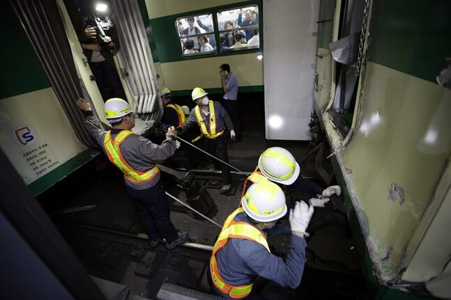 South Korea's subway workers try to repair a train after its collision at Sangwangshipri station in Seoul, South Korea, Friday, May 2, 2014. A subway train ran into another train at the station Friday, causing minor injuries for scores of people, a city official said. (AP Photo/Lee Jin-man)