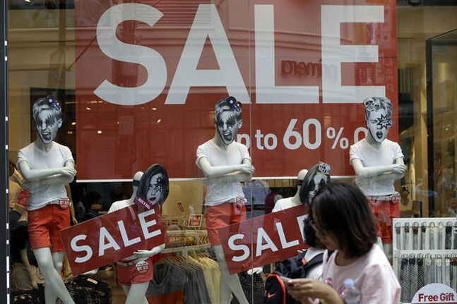 A woman walks by sale signs at Seoul shopping district, South Korea, Thursday, July 24, 2014. South Korea's government unveiled stimulus plans Thursday after the shock of a deadly ferry sinking slowed economic growth to the lowest level in three quarters. (AP Photo/Lee Jin-man)