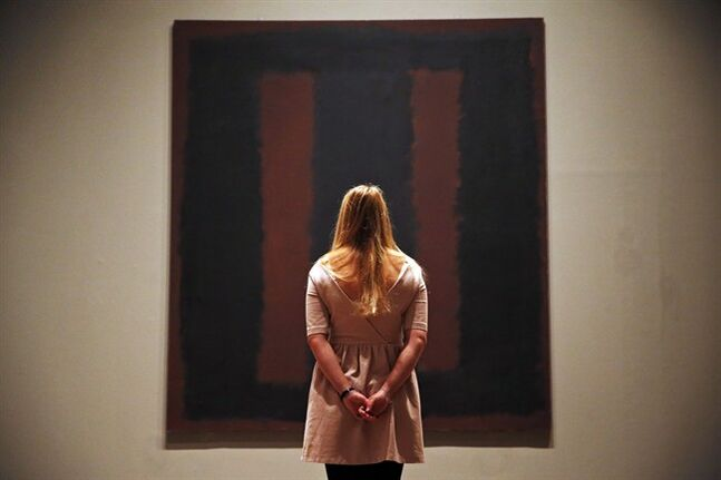 A Tate Modern employee poses for the photographers in front of Mark Rothko's mural 'Black on Maroon', in London, Tuesday, May 13, 2014. Tate Modern is putting the mural back on display Tuesday, more than a year and a half after it was defaced with black ink by a vandal trying to draw attention to an obscure artistic movement. The gallery has spent 18 months working on the abstract painting, whose surface is made up of layers of oil, pigment, resin, egg and glue. Tate experts said the ink soaked in as far as the back of the canvas, requiring delicate work to remove it and restore the painting's layers. Wlodzimierz Umaniec received a two-year jail sentence for scrawling