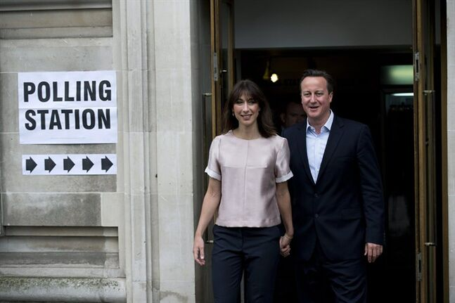 Britain's Prime Minister and leader of the Conservative Party David Cameron and his wife Samantha pause to pose for photographers and television cameras as they leave after casting their votes at a polling station in central London, Thursday, May 22, 2014. Voters in 28 countries on Thursday begin choosing the next European Parliament and helping determine the EU's future leaders and course. Around 400 million Europeans are eligible to take part in what is termed the world's largest cross-border exercise in representative democracy. (AP Photo/Matt Dunham)