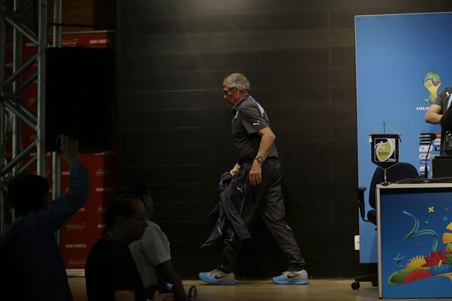 Uruguay's head coach Oscar Tabarez leaves after making a statement during a press conference the day before the round of 16 World Cup soccer match between Colombia and Uruguay at the Maracana Stadium in Rio de Janeiro, Brazil, Friday, June 27, 2014. FIFA banned Uruguay striker Luis Suarez from all football activities for four months on Thursday for biting an opponent at the World Cup, a punishment that rules him out of the rest of the tournament and the start of the upcoming Premier League season. (AP Photo/Matt Dunham)