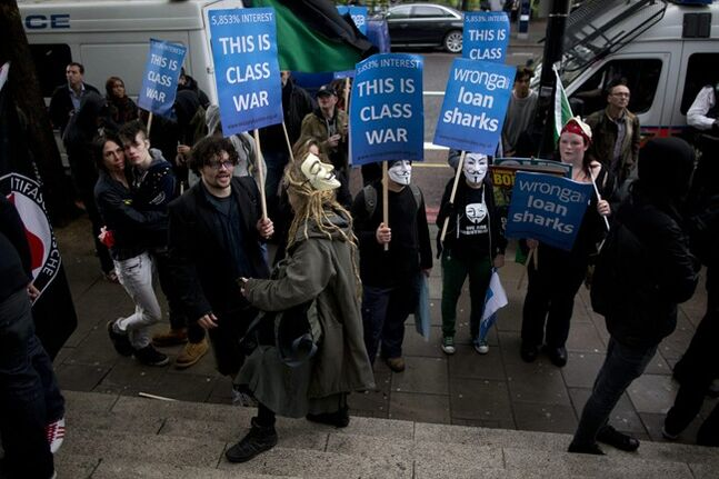 FILE - In this Thursday, May 1, 2014 file photo, demonstrators hold placards campaigning against the short term loans company Wonga outside their offices in London, during a May Day protest. Britain's financial regulator on Thursday, July 15, 2014 has announced new limitations on what payday lenders can charge their customers, the latest step in moves to tackle poor conduct in the short-term credit industry. (AP Photo/Matt Dunham, File)