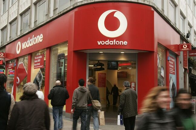 FILE - This Tuesday, Feb. 24, 2009 file photo shows people walking by a branch of Vodafone in central London. Vodafone, one of the world's largest cellphone companies, revealed the scope of government snooping into phone networks Friday, saying authorities in some countries are able to directly access an operator's network without seeking permission.The company outlined the details in a report that is described as the first of its kind, covering 29 countries in which it directly operates. It gives the most comprehensive look to date on how governments monitor the communications of their citizens. The most explosive revelation was that in a small number of countries, authorities require direct access to an operator's network — bypassing legal niceties like warrants. It did not name the countries. (AP Photo/Sang Tan, file)