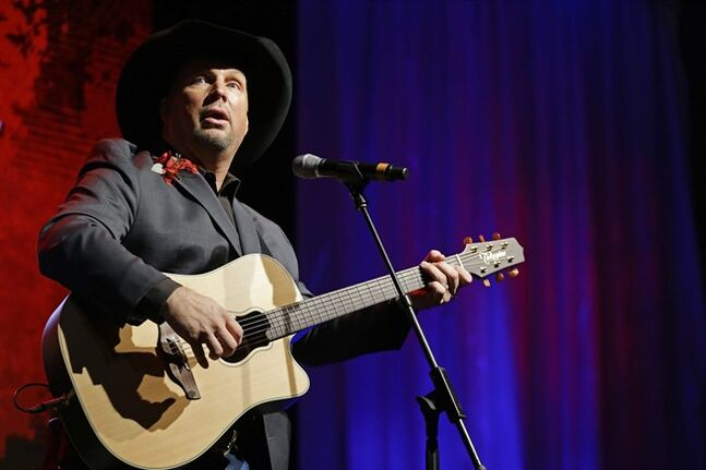 FILE - In this Sunday, Oct. 7, 2012 file photo, Garth Brooks performs during the Nashville Songwriters Hall of Fame inductions in Nashville, Tenn. Like an ill-fated romance in a country song, Garth Brooks and Dublin just weren't meant to be. Promoters say five Irish concerts by the country music star have been canceled after a battle between venue owners and local residents. More than 400,000 tickets had been sold for the gigs, due to start at Croke Park stadium on July 25. The stint had been billed as a