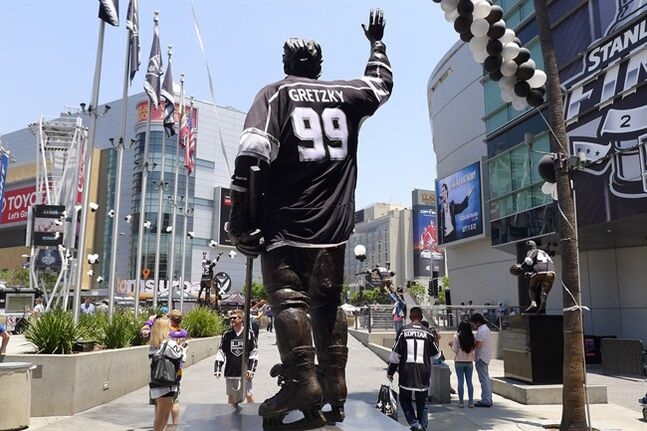 People walk pass a Wayne Gretzky statue as they arrive for game 2 in the NHL hockey Stanley Cup Finals between the Los Angeles Kings and the New York Rangers in Los Angeles, Saturday, June 7, 2014. THE CANADIAN PRESS/Neil Davidson