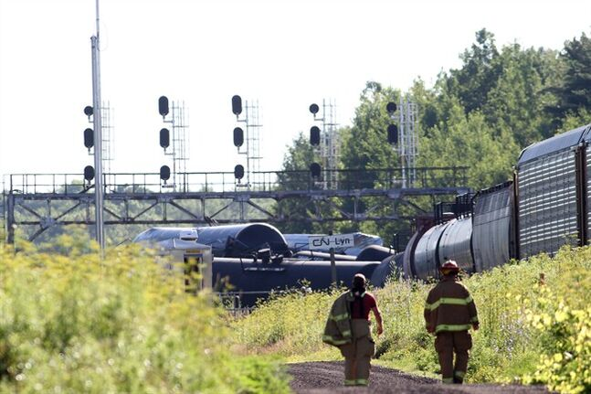 Fire fighters walk near the derailed train near Brockville, Ont., on Thursday July 10, 2014, after 26 cars jumped the tracks.THE CANADIAN PRESS/Lars Hagberg