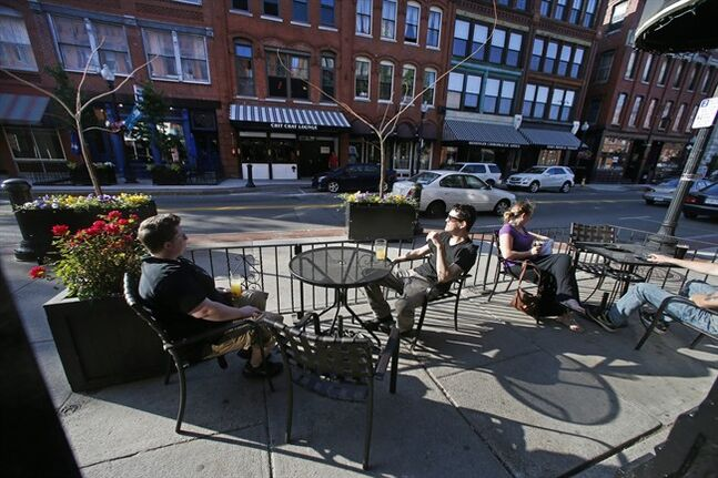 In this Tuesday, June 3, 2014 photo, people enjoy drinks with a view of Washington Street at the Tap Brewing Company in Haverhill, Mass. Haverhill is a northern Massachusetts city of 60,000 people, that after years of sliding down market, clearly is hungry for a bit of renewal and reinvention. (AP Photo/Elise Amendola)