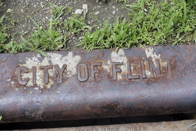 In a June 12, 2014 photo in Flint, Mich., a city of Flint storm drain is seen on the city's west side. As Detroit hopes to ride out of bankruptcy this year, a smaller Michigan city with a similarly strong bond to the automotive industry soon could drive in. Flint, like its bankrupt big brother an hour's drive south, has suffered a spectacular drop in population and factory jobs with a corresponding rise in property abandonment and crime. (AP Photo/Carlos Osorio)