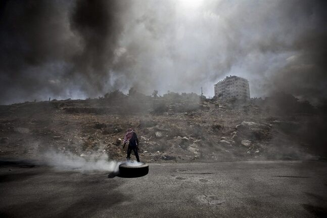 A Palestinian man burns a tire during clashes with Israeli soldiers following a protest against the Israeli offensive in Gaza, outside Ofer, an Israeli military prison near the West Bank city of Ramallah, Friday, July 18, 2014. Israeli troops pushed deeper into Gaza on Friday to destroy rocket launching sites and tunnels, firing volleys of tank shells and clashing with Palestinian fighters in a high-stakes ground offensive meant to weaken the enclave's Hamas rulers. (AP Photo/Majdi Mohammed)