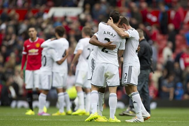 Swansea City's players celebrate after their 2-1 win over Manchester United in their English Premier League soccer match at Old Trafford Stadium, Manchester, England, Saturday Aug. 16, 2014. (AP Photo/Jon Super)
