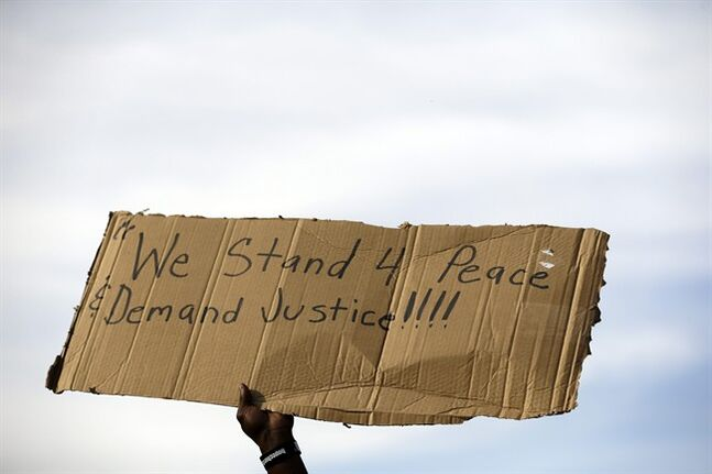 A demonstrator holds up a sign Thursday, Aug. 14, 2014, at the site where Michael Brown was shot and killed by police in Ferguson, Mo. The Missouri Highway Patrol seized control of a St. Louis suburb Thursday, stripping local police of their law-enforcement authority after four days of clashes between officers in riot gear and furious crowds protesting the death of an unarmed black teen shot by an officer. (AP Photo/Jeff Roberson)