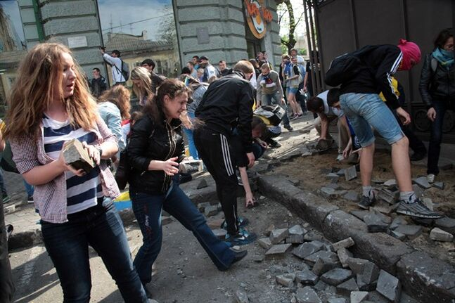 Ukrainian government supporters dig for stones during a clash with pro-Russians in the Black Sea port of Odessa, Ukraine, Friday, May 2, 2014. A clash broke out late Friday between pro-Russians and government supporters in Odessa, on the Black Sea coast some 550 kilometers (330 miles) from the turmoil in the east. Odessa had remained largely untroubled by unrest since the February toppling of pro-Russia President Viktor Yanukovych, which ignited tensions in the east. (AP Photo/Sergei Poliakov)