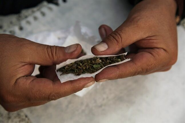 In this Aug. 4, 2013 photo, a man identified only as Pedro prepares a marijuana cigarette at his home in Mexico City. A group of leftist Mexico City lawmakers have introduced a bill, Thursday Feb 13, 2014, to legalize the sale of marijuana in the nation's capital. Since 2009, Mexico has allowed the possession of 5 grams of marijuana, about four joints, for personal use. (AP Photo/Marco Ugarte)