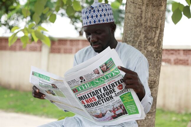 Shehu Haruna reads a local newspaper with headlines declaring that the Military were alerted before the abducution of secondary school girls in Chibok, on a street in Abuja, Nigeria, Saturday, May 10, 2014. The weakness of the Nigerian armed forces was highlighted Friday in a report which said the military did not respond to warnings that Boko Haram rebels were about to attack Chibok, the town where the young women were abducted from their school. Nigerian security forces had four hours notice about the April 15 attack by the rebels but did not react because of their fear of engaging the extremists, said Amnesty International, in a report citing multiple interviews with credible sources.(AP Photo/Sunday Alamba)