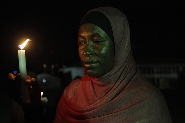 A woman holds a candle during a vigil in Abuja, Nigeria, on Wednesday, May 14, 2014, to mark one month since the girls of government secondary school Chibok were kidnapped in the northeastern state of Borno. Nigeria's government is ruling out an exchange of more than 270 kidnapped schoolgirls for detained Islamic militants, Britain's top official for Africa said Wednesday. (AP Photo/Sunday Alamba)