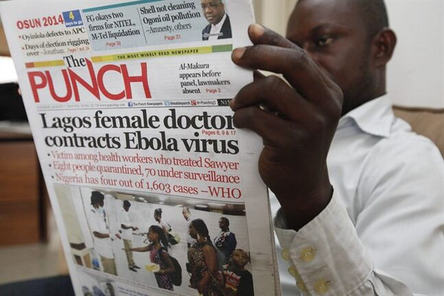 A man reads a local newspaper with headline news about a Lagos female doctor contracts Ebola Virus, in Lagos, Nigeria, Tuesday, Aug. 5, 2014. Lagos State Health Commissioner Jide Idris announced Tuesday that eight people are being kept in quarantine with symptoms of Ebola. (AP Photo/Sunday Alamba)