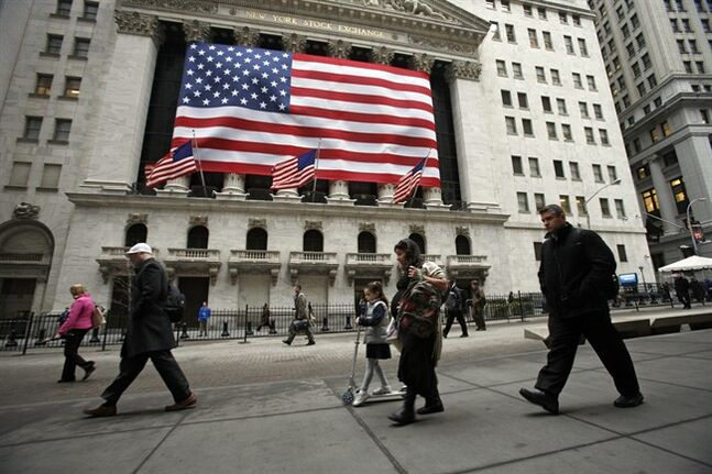 People pass in front of the New York Stock Exchange in this Monday, March 9, 2009 photo. Worries over Russian troops amassing near the Ukraine border caused a sharp sell-off in global stock markets on Wednesday Aug. 6, 2014. (AP Photo/Mark Lennihan)