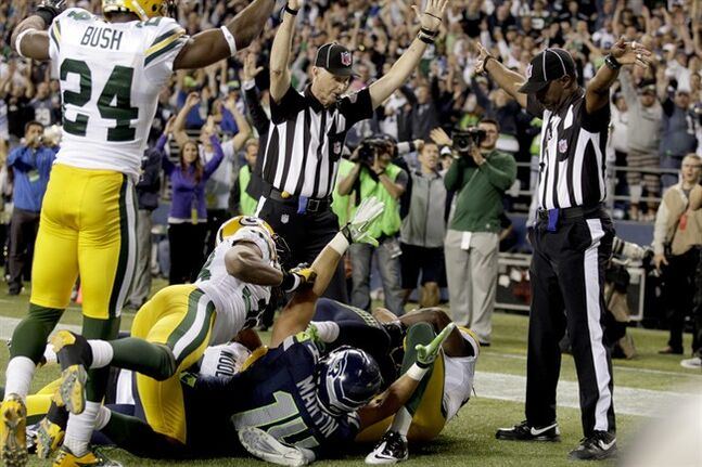 FILE - In this Sept. 24, 2012, file photo, an official, rear center, signals for a touchdown by Seattle Seahawks wide receiver Golden Tate, obscured, as another official, at right, signals a touchback, on the controversial last play of an NFL football game against the Green Bay Packers in Seattle. It's been nearly two full years since the Packers and Seahawks met in the regular season, a game that forever became known as the