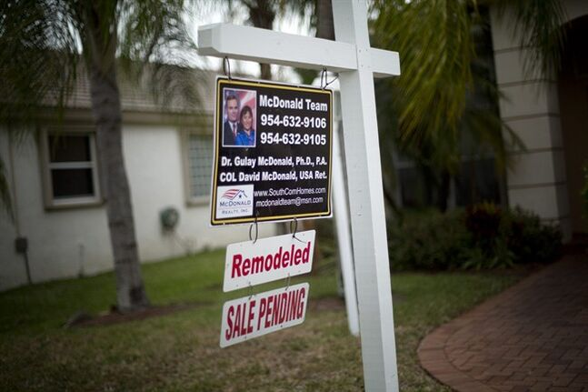 In this March 17, 2014 photo, a for sale sign hangs outside a home in Pembroke Pines, Fla. The National Association of Realtors on Monday, April 28, 2014 said its seasonally adjusted pending home sales index rose 3.4 percent to 97.4 last month. Still, the index remains 7.9 percent below its level a year ago. (AP Photo/J Pat Carter)