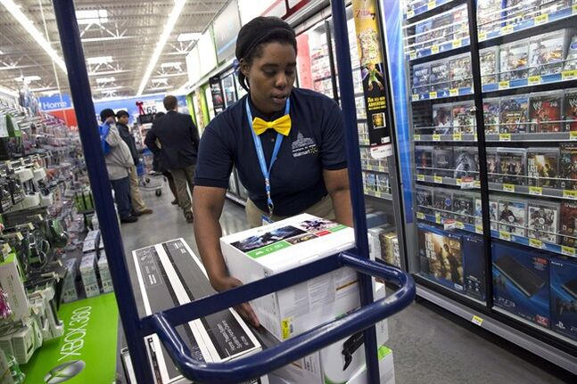 FILE - In this Wednesday, Dec. 4, 2013, photo, Tracey Anderson, 26, re-stocks X-Box sets on opening day of a new Wal-Mart on Georgia Avenue Northwest in Washington. Wal-Mart reports quarterly earnings on Thursday, Feb. 20, 2014. (AP Photo/Jacquelyn Martin. File)