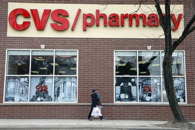 In this March 25, 2014 photo, a pedestrian passes a a CVS store in Philadelphia. CVS reports quarterly earnings on Friday, May 2, 2014. (AP Photo/Matt Rourke)