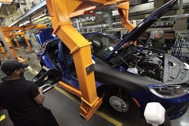 In this March 14, 2014 photo, an assembly line worker builds a 2015 Chrysler 200 automobile at the Sterling Heights Assembly Plant in Sterling Heights, Mich. Chrysler Group LLC reports quarterly earnings on Monday, May 12, 2014. (AP Photo/Paul Sancya)