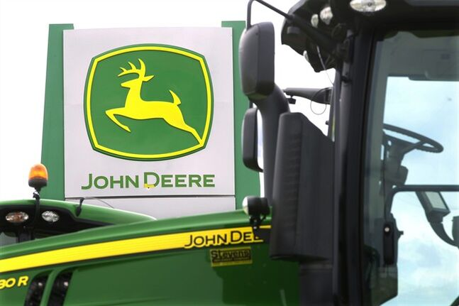This Sunday, June 8, 2014 photo shows John Deere farming equipment at a dealership in Petersburg, Ill. Deere & Co. reports quarterly financial results before the market opens Wednesday, Aug. 13, 2014. (AP Photo/Seth Perlman)