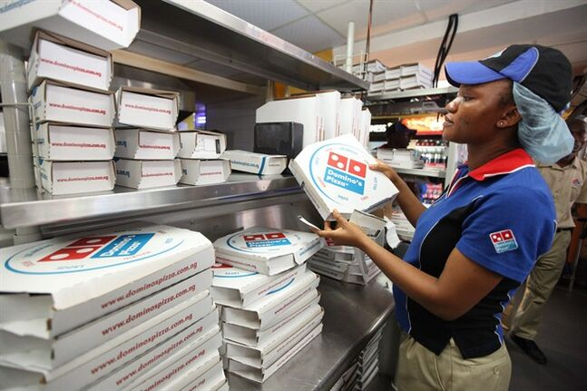 FILE - In this file photo taken Sunday, Feb. 10, 2013, a worker prepares boxes at a Domino's pizza restaurant in Lagos, Nigeria. After having been plagued with a reputation for tasting generic and manufactured, the Ann Arbor, Mich.-based chain has been enjoying strong sales and growth overseas boasting nearly 6,000 international locations. ( AP Photo/Sunday Alamba, File)
