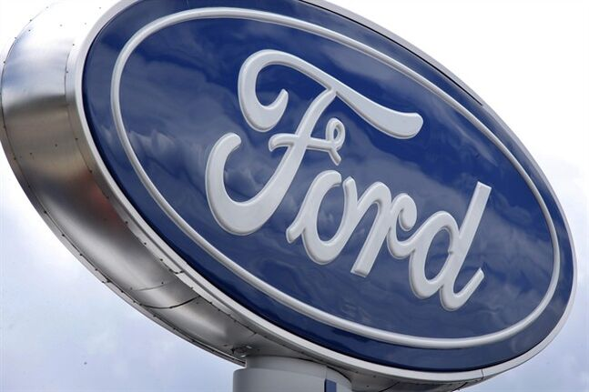 In this photo made on Thursday, June 5, 2014, clouds are reflected in the Ford sign at a dealership in Wexford, Pa. The National Highway Traffic Safety Administration says it is investigating steering problems in about 500,000 Ford cars. The investigation covers 2004 to 2007 Crown Victoria, Grand Marquis and Marauder models. (AP Photo/Keith Srakocic)