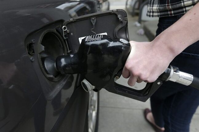 FILE - In this April 29, 2014 photo, a customer fills her car with fuel at a gas station, in Brookline, Mass. Gasoline prices are falling along with oil prices this summer because concerns of global supply disruptions have subsided somewhat despite continued violence in the Middle East. (AP Photo/Steven Senne, File)