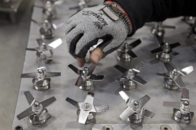 In this April 15, 2014 photo, Evelyn Morales assembles blender blades at the Vitamix manufacturing facility in Strongsville, Ohio. The Labor Department releases the Producer Price Index for June on Wednesday, July 16, 2014.(AP Photo/Mark Duncan)