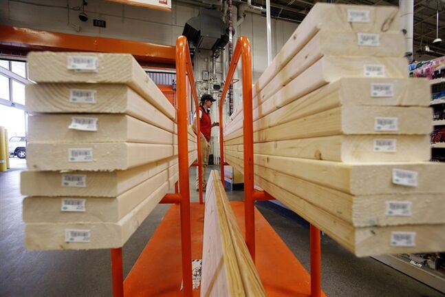 In this May 17, 2014 photo, a shopper checks out with her lumber at a Home Depot in Boston. Home Depot reports quarterly financial results Tuesday, Aug. 19, 2014. (AP Photo/Gene J. Puskar)
