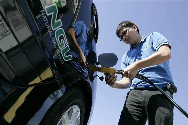 FILE - In this Sept. 4, 2008, file photo, Garvin Cui fuels up his natural gas vehicle at a Clean Energy station in San Francisco. New technology has unlocked vast reserves of natural gas in deep rock formations, creating a natural gas glut that has depressed prices. That makes natural gas more attractive as a transportation fuel. (AP Photo/Marcio Jose Sanchez, File)