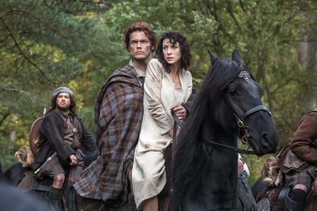 This image released by Starz shows Sam Heughan, center left, and Caitriona Balfe in a scene from
